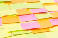 Ciérrese para arriba de muchas etiquetas engomadas coloridas en la madera Fotos de archivo libres de regalías