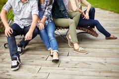Ciérrese para arriba de muchas piernas que se sientan en banco en el parque Imagen de archivo libre de regalías