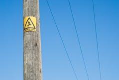 Ciérrese para arriba de muestra del peligro en poste de la electricidad Fotos de archivo libres de regalías