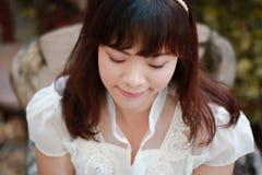 Ciérrese para arriba de mujer bastante asiática de los jóvenes en el vestido blanco con el jardín Imagenes de archivo