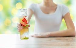 Ciérrese para arriba de mujer con agua de la fruta en la botella de cristal Imagen de archivo libre de regalías