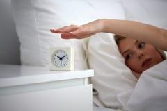 Ciérrese para arriba de mujer con el despertador en cama en casa Fotografía de archivo libre de regalías