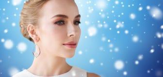 Ciérrese para arriba de mujer con el pendiente de la perla sobre nieve Imagenes de archivo