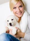 Ciérrese para arriba de mujer con el perrito blanco en sus rodillas Fotografía de archivo