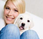 Ciérrese para arriba de mujer con el perrito lindo en sus rodillas foto de archivo libre de regalías
