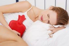 Ciérrese para arriba de mujer con la botella de agua caliente en cama Imagen de archivo