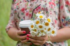 ciérrese para arriba de mujer con la taza de café con las flores en parque Foto de archivo