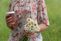 ciérrese para arriba de mujer con la taza de café con las flores en parque Fotografía de archivo