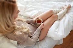 Ciérrese para arriba de mujer con la taza de té en cama Foto de archivo