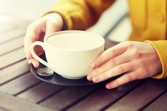 Ciérrese para arriba de mujer con la taza del cacao en el café de la calle Fotos de archivo