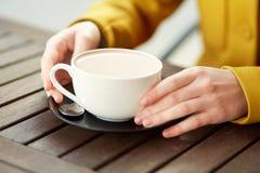 Ciérrese para arriba de mujer con la taza del cacao en el café de la calle Imagenes de archivo