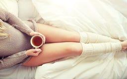 Ciérrese para arriba de mujer con la taza de té en cama Imagen de archivo
