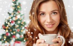 Ciérrese para arriba de mujer con la taza de té sobre el árbol de navidad Imagen de archivo