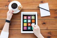 Ciérrese para arriba de mujer con PC de la tableta en la tabla de madera Imagenes de archivo