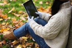 Ciérrese para arriba de mujer con PC de la tableta en parque del otoño Imagen de archivo