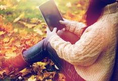 Ciérrese para arriba de mujer con PC de la tableta en parque del otoño Fotografía de archivo