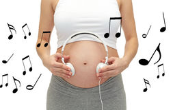 Ciérrese para arriba de mujer embarazada y de auriculares en la panza Imagen de archivo libre de regalías