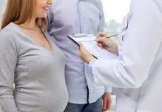 Ciérrese para arriba de mujer embarazada y de doctor felices Fotografía de archivo