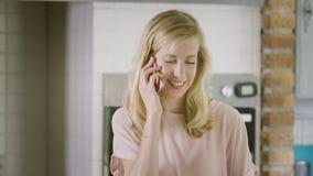 Ciérrese para arriba de mujer en la cocina que hace una llamada con su sonrisa del smartphone almacen de video