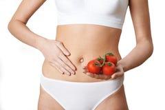 Ciérrese para arriba de mujer en la ropa interior que sostiene los tomates y que toca Sto imagen de archivo libre de regalías