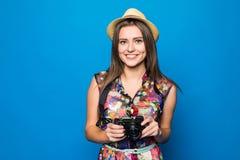 Ciérrese para arriba de mujer en sombrero en el fondo azul que toma una foto con la cámara digital Imágenes de archivo libres de regalías