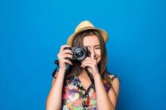 Ciérrese para arriba de mujer en sombrero en el fondo azul que toma una foto con la cámara digital Fotografía de archivo