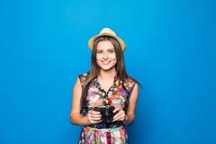 Ciérrese para arriba de mujer en sombrero en el fondo azul que toma una foto con la cámara digital Imagenes de archivo
