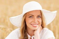 Ciérrese para arriba de mujer feliz en sombrero del sol en campo de cereal Imagen de archivo libre de regalías