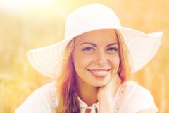 Ciérrese para arriba de mujer feliz en sombrero del sol en campo de cereal Fotografía de archivo
