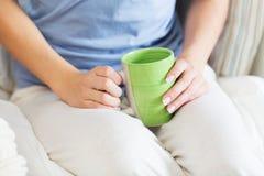 Ciérrese para arriba de mujer joven con la taza de té Foto de archivo libre de regalías