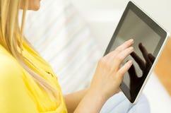 Ciérrese para arriba de mujer joven con PC de la tableta en casa Imagen de archivo