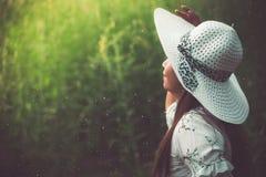 Ciérrese para arriba de mujer de la belleza con el sombrero blanco del vestido y del ala en yo fotografía de archivo