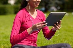 Ciérrese para arriba de mujer sonriente con PC de la tableta al aire libre Fotos de archivo