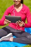 Ciérrese para arriba de mujer sonriente con PC de la tableta al aire libre Imagenes de archivo
