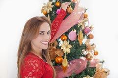 Ciérrese para arriba de mujer sonriente hermosa delante del adornamiento de un árbol de navidad, del feliz christmast y del conce Imagen de archivo libre de regalías