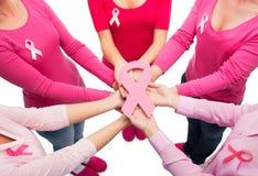 Ciérrese para arriba de mujeres con las cintas de la conciencia del cáncer Imagen de archivo libre de regalías