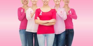 Ciérrese para arriba de mujeres con las cintas de la conciencia del cáncer Foto de archivo