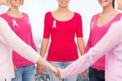 Ciérrese para arriba de mujeres con las cintas de la conciencia del cáncer Fotos de archivo libres de regalías