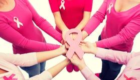 Ciérrese para arriba de mujeres con las cintas de la conciencia del cáncer Imágenes de archivo libres de regalías