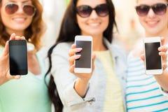 Ciérrese para arriba de mujeres jovenes felices con smartphone Fotografía de archivo