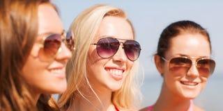 Ciérrese para arriba de mujeres jovenes sonrientes en gafas de sol Imagenes de archivo