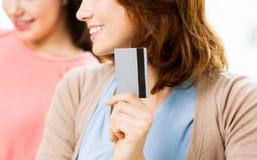 Ciérrese para arriba de mujeres o de amigos con la tarjeta de crédito Imagen de archivo libre de regalías