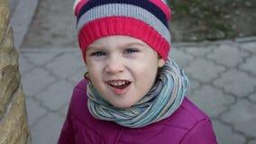 Ciérrese para arriba de niña caucásica hermosa con los ojos azules hermosos que llevan el sombrero rayado, mirando la cámara metrajes