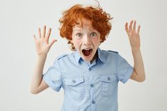 Ciérrese para arriba de niño pequeño bonito con el pelo y las pecas del jengibre que separan las manos, gritando en alta voz, int Imagen de archivo libre de regalías