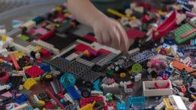 Ciérrese para arriba de niño que la mano rápidamente recoge piezas del juguete de la construcción Acelere Timelapse almacen de video