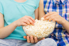 Ciérrese para arriba de niños con la consumición del cuenco de las palomitas Imagenes de archivo