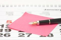 Ciérrese para arriba de nota de post-it sobre calendario Foto de archivo libre de regalías