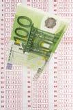 Ciérrese para arriba de nota del euro 100 y de boleto de apuestas Imagen de archivo