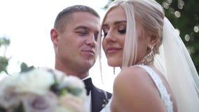Ciérrese para arriba de novio y de novia Pares hermosos de la boda en el parque Recienes casados elegantes almacen de video