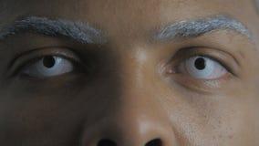 Ciérrese para arriba de ojos del hombre afroamericano con las lentes de ojo blancas almacen de video